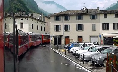 The Bernina Express leaves Tirano through the streets