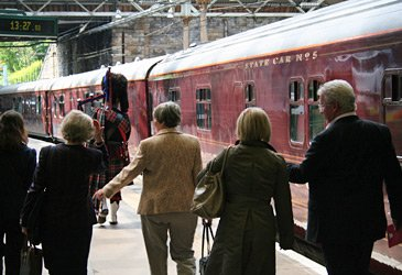 A piper leads the way to the Royal Scotsman train at Edinburgh