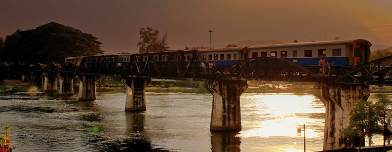 Evening local train crossing the Bridge on the River Kwai