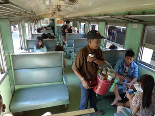 3rd class seats on a Thai train, with a vendor selling soft drinks & beer.