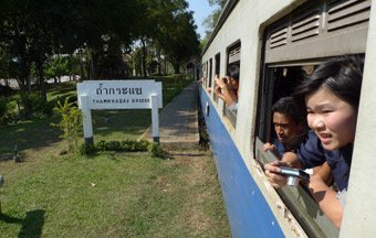 A train from Nam Tok to River Kwai Bridge, Kanchanaburi & Bangkok calls at Thamkrasae Bridge station
