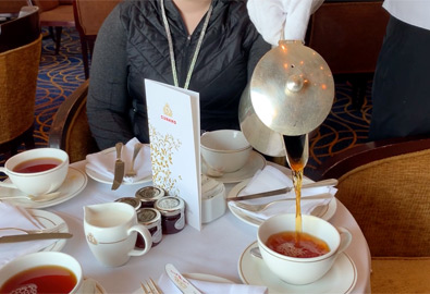 A white-gloved steward pours the tea on QM2