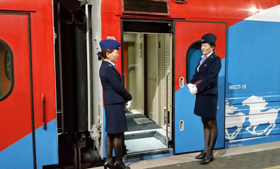Staff greet passengers at the door of Trans-Siberian train 6